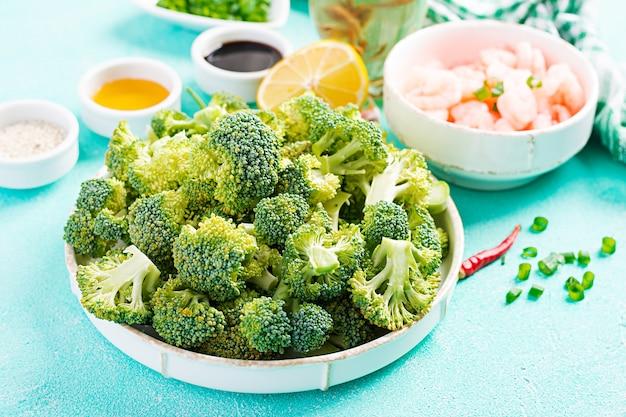 De ingrediënten voor het koken bewegen gebraden gerechtgarnalen met broccoli dicht omhoog op een lijst. garnalen en broccoli.