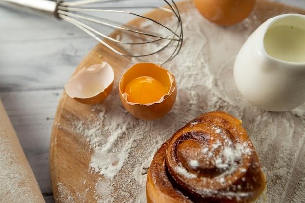 De ingrediënten voor het maken van gebak op tafel zijn tarwemeel, eieren, melk, een deegroller en een houten plank