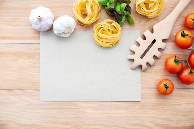 De ingrediënten voor huisgemaakte pasta met kopie ruimte op houten tafel.