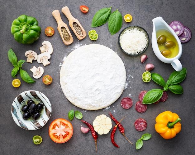 De ingrediënten voor zelfgemaakte pizza op donkere stenen achtergrond.