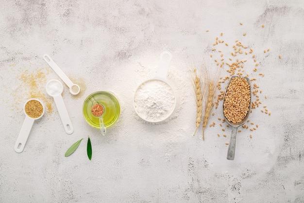 De ingrediënten voor zelfgemaakte pizzadeeg met tarweoren, tarwebloem en olijfolie op een witte betonnen ondergrond. bovenaanzicht en kopieer ruimte.