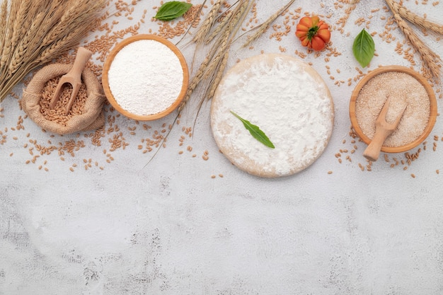 De ingrediënten voor zelfgemaakte pizzadeeg met tarweoren, tarwemeel en tarwekorrels opgezet op witte betonnen ondergrond.