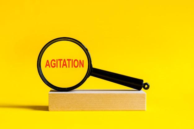 De inscriptie agitatie door vergrootglas op gele achtergrond. het vergrootglas is gemonteerd op een houten standaard op een tafel