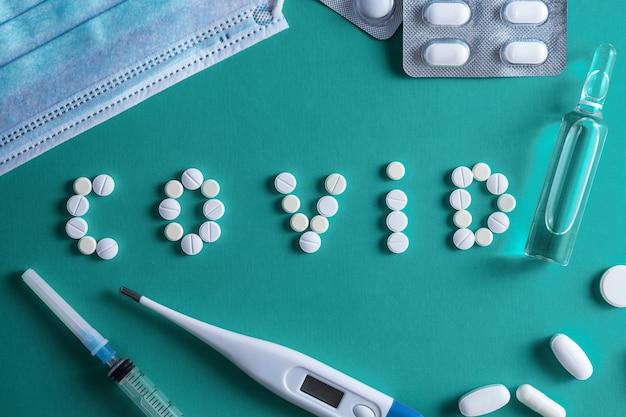 De inscriptie covid, gemaakt van witte ronde tabletten. wegwerp spuit en flacon drug op een rode achtergrond. covid-19 coronavirus-vaccin. ruimte voor tekst