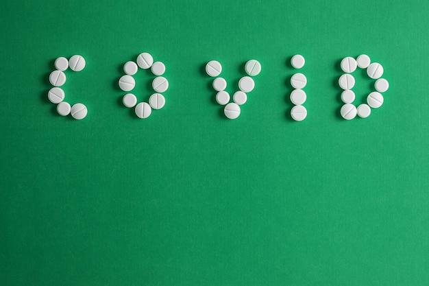 De inscriptie covid van pillen op een groen oppervlak