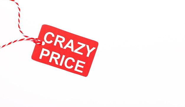 De inscriptie crazy price op een rood prijskaartje op een lichte achtergrond. reclameconcept. ruimte kopiëren