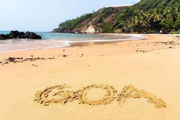 De inscriptie goa op een zandstrand tegen de blauwe zee en het turquoise water en de golven