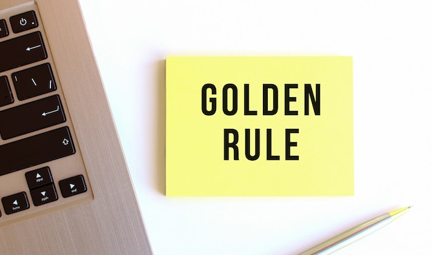 De inscriptie gouden regel op de gele plaknotities in de buurt van de laptop op het witte bureau.
