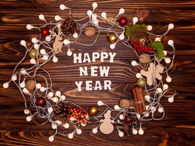 De inscriptie happy new year, krans gemaakt van kerstversiering