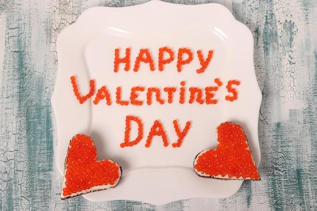 De inscriptie happy valentine's day van rode kaviaar op een witte plaat met canapés, bovenaanzicht