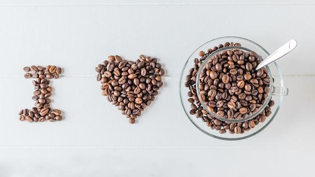 De inscriptie i love bekleed met koffiebonen op een witte houten tafel. het uitzicht vanaf de top. plat liggen. granen voor de bereiding van het populaire drankje.