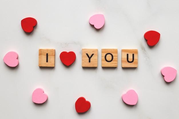 De inscriptie i love you gemaakt van houten letters en hartjes. valentijnsdag concept.