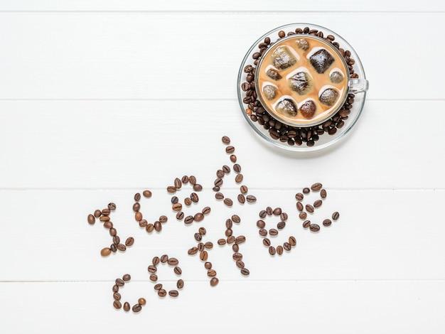 De inscriptie ijskoffie en een kopje afgewerkt drankje op een witte tafel. verfrissende en verkwikkende drank van koffiebonen en melk. het uitzicht vanaf de top. plat liggen.