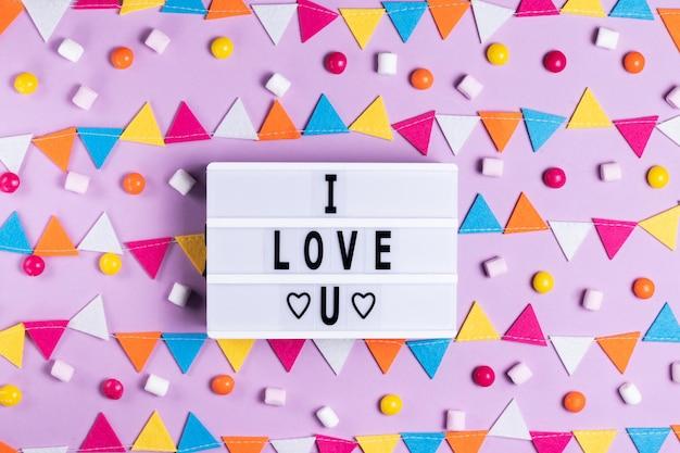 De inscriptie ik hou van je wenskaart voor valentijnsdag en valentijnsdag op een wit bord op een roze achtergrond met een veelkleurige slinger vakantie