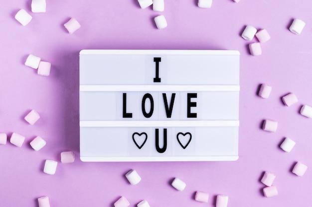 De inscriptie ik hou van je wenskaart voor valentijnsdag en valentijnsdag op een wit bord op een roze achtergrond met witte en roze marshmallows romantische vakantie