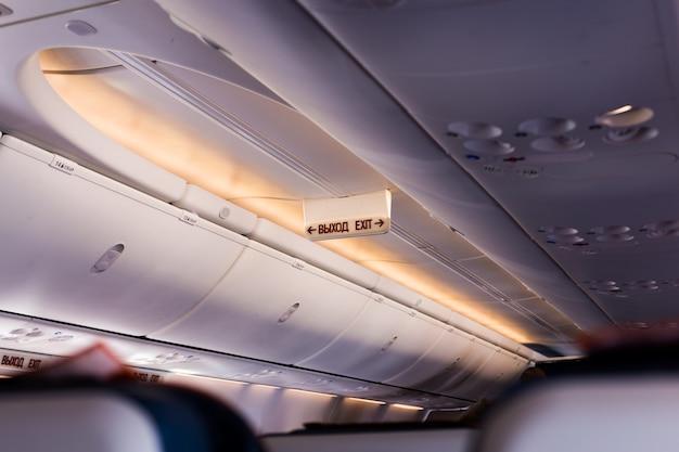 De inscriptie in de cabine van het vliegtuig op het scorebord op de waarschuwingsactie, de uitgang van het vliegtuig.