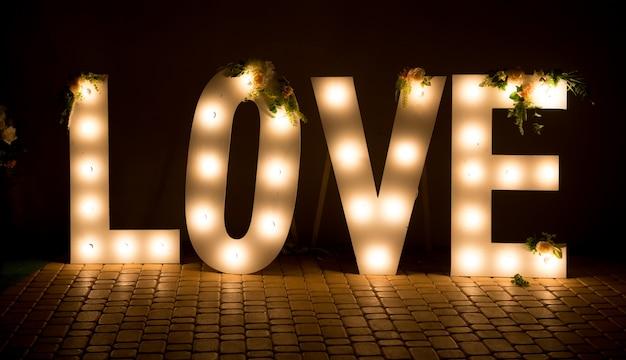 De inscriptie is liefde. gloeiende grote letters. bruiloft decoraties.