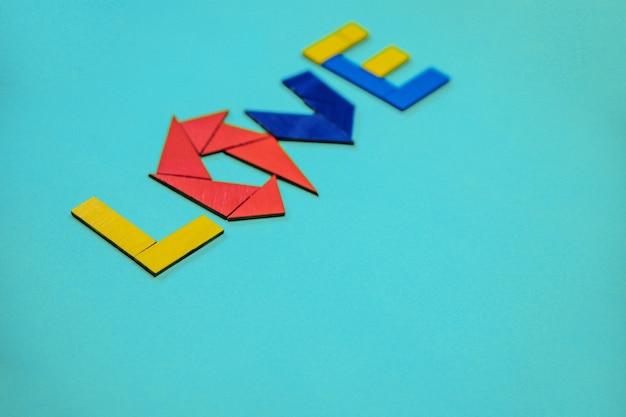 De inscriptie liefde. gekleurde letters gemaakt van houten geometrische vormen. het concept van valentijnsdag en bruiloft.