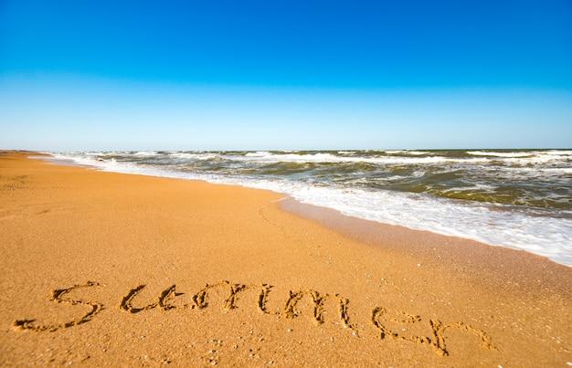 De inscriptie op de zandzomer in de buurt van de stormachtige zeegolf op een zonnige warme zomerdag. concept van de langverwachte zomervakantie en vakantie