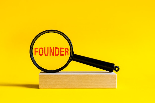 De inscriptie oprichter door vergrootglas op gele achtergrond. het vergrootglas is gemonteerd op een houten standaard op een tafel