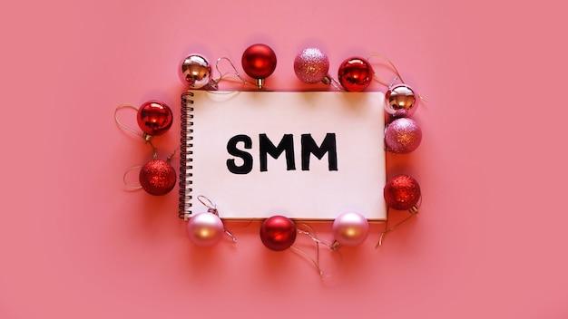 De inscriptie smm in een notitieboekje op een roze feestelijke achtergrond. rode en roze kerstballen.