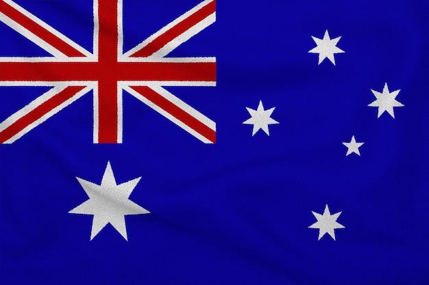 De inscriptie van australië op de handen van de kinderen tegen de achtergrond van een wapperende vlag van oostenrijk.
