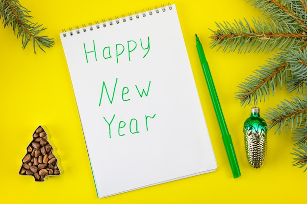 De inscriptie van het happy new year op de achtergrond van vuren takken, kegels en vuren noten.