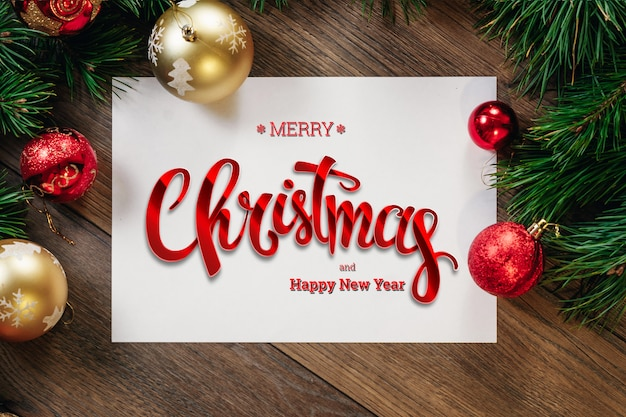 De inscriptie van merry christmas, groene vuren takken, decoraties, a4-blad op een houten bruine tafel. kerstkaart, vakantie. gemengde media.