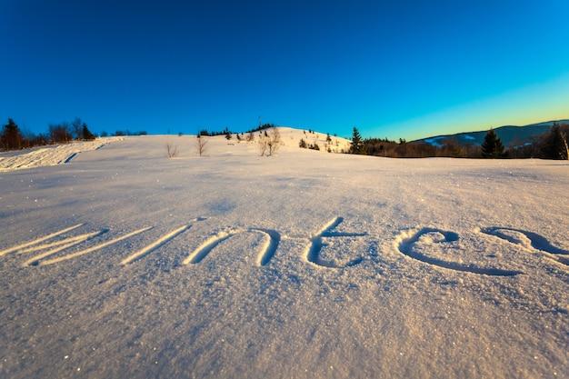 De inscriptie winter op sneeuw tegen de achtergrond van het bos en de heuvels op een zonnige ijzige winterdag.