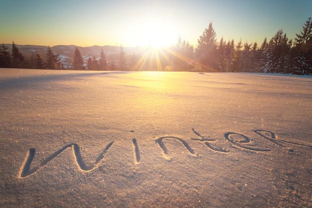 De inscriptie winter op sneeuw tegen de achtergrond van het bos en de heuvels