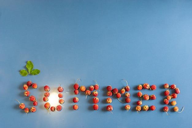 De inscriptie zomer bekleed met aardbeien op een keramische tegel met een stoftextuur. een blad boven de letter c. licht van een gloeilamp zoals de zon in de letter u. vlakke weergave. bos aardbei.