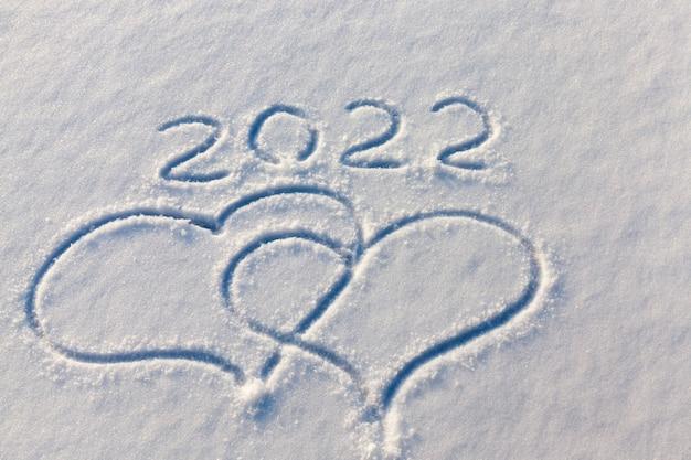 De inscripties over het nieuwe jaar het winterseizoen van eind 2021 en het begin van 2022, de inscriptie over het nieuwe jaar 2022 op de sneeuw in de winter