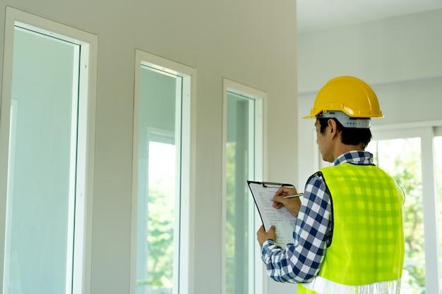 De inspecteur of ingenieur controleert de bouwconstructie en de volgorde in het huis.