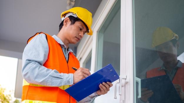 De inspecteur of ingenieur controleert de bouwstructuur en de deurspecificaties. nadat de renovatie is voltooid