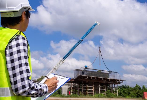 De inspecteurs of ingenieurs controleren het werk van het aannemersteam om een brug over de weg te bouwen.