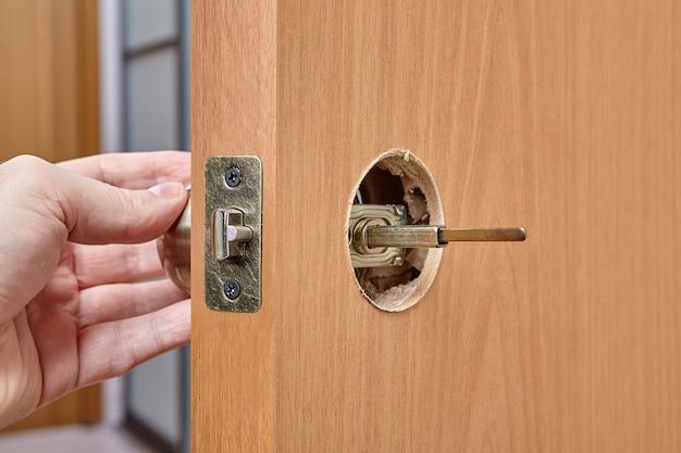 De installateur duwt de spil van de deurgreep door het gat in de vergrendelingsconstructie en de voorkant.