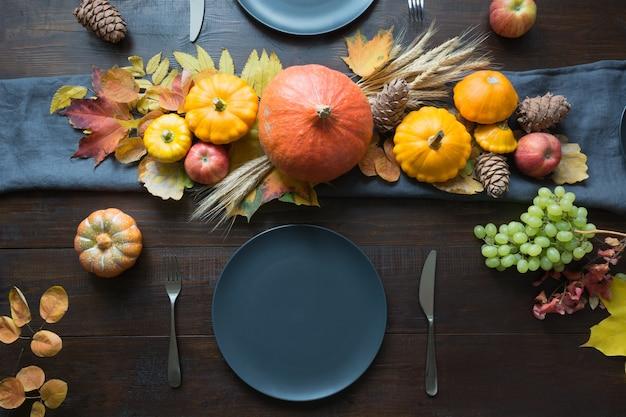De instelling van de herfsttafel met bladeren, slinger en pompoenen, bovenaanzicht