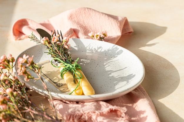De instelling van de paastafel met bord, bestek en roze bloemen