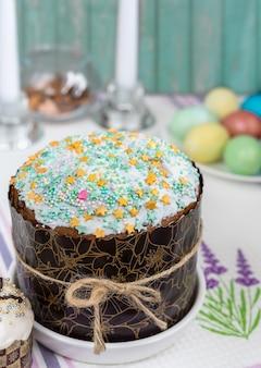 De instelling van de paastafel met traditionele bundtcake, kleurrijke eieren, kaarsen en tafelkleed
