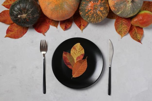 De instelling van de tabel op thanksgiving day ingericht pompoen, peren en kleurrijke bladeren op grijs. uitzicht van boven
