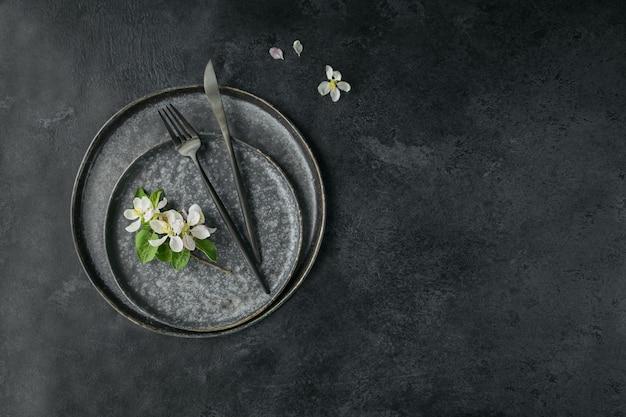 De instelling van de tabel van de plaats van de lente met bloeiende takken van de appelboom en bloemen op zwarte tafel