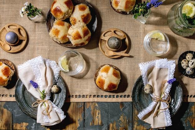 De instelling van de tabel van pasen met gekleurde en chocolade-eieren, warme kruisbroodjes, boeket bloemen, lege keramische plaat met servet, glas limonade drankje op houten tafel met textiel tafelkleed. plat leggen
