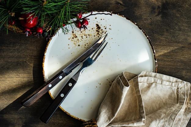 De instelling van de tabel voor het kerstdiner op houten tafel