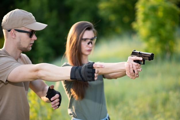 De instructeur leert het meisje op een pistool schieten op het bereik