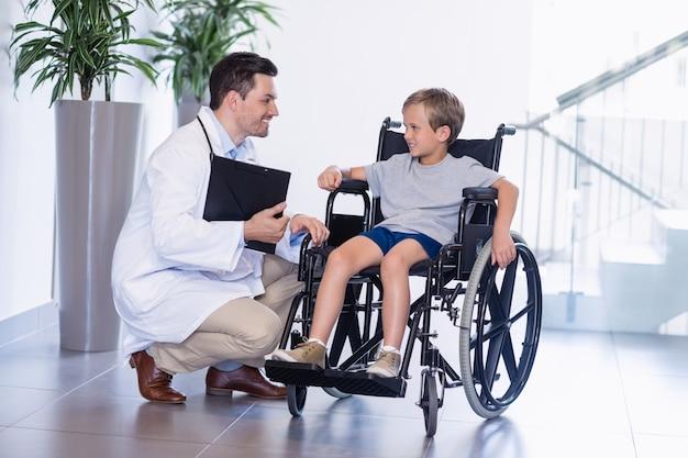 De interactie van de arts met schakelt jongen in gang uit