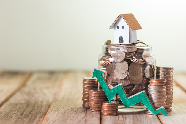 De investering van het huis, die geld voor hypotheek, muntstukken in een glaskruik spaart op houten lijstachtergrond