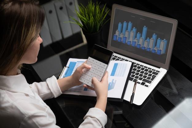 De investeringsadviseur die van de onderneemster de financiële balans van het bedrijf jaarlijks financieel rapport analyseert