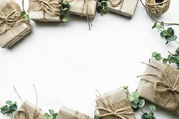 De inzameling van giftdozen verpakt in minimale stijl van kraftpapier met bladeren op witte achtergrond.