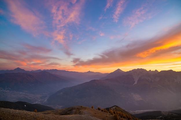 De italiaanse franse alpen bij zonsondergang. kleurrijke lucht boven de majestueuze bergtoppen, droog kaal terrein en groene valleien.