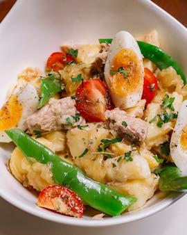 De italiaanse kom van de aardappelsalade met van de de kersentomaat van tonijnbonen de peterselie gekookte eieren en olijfolieverticaal